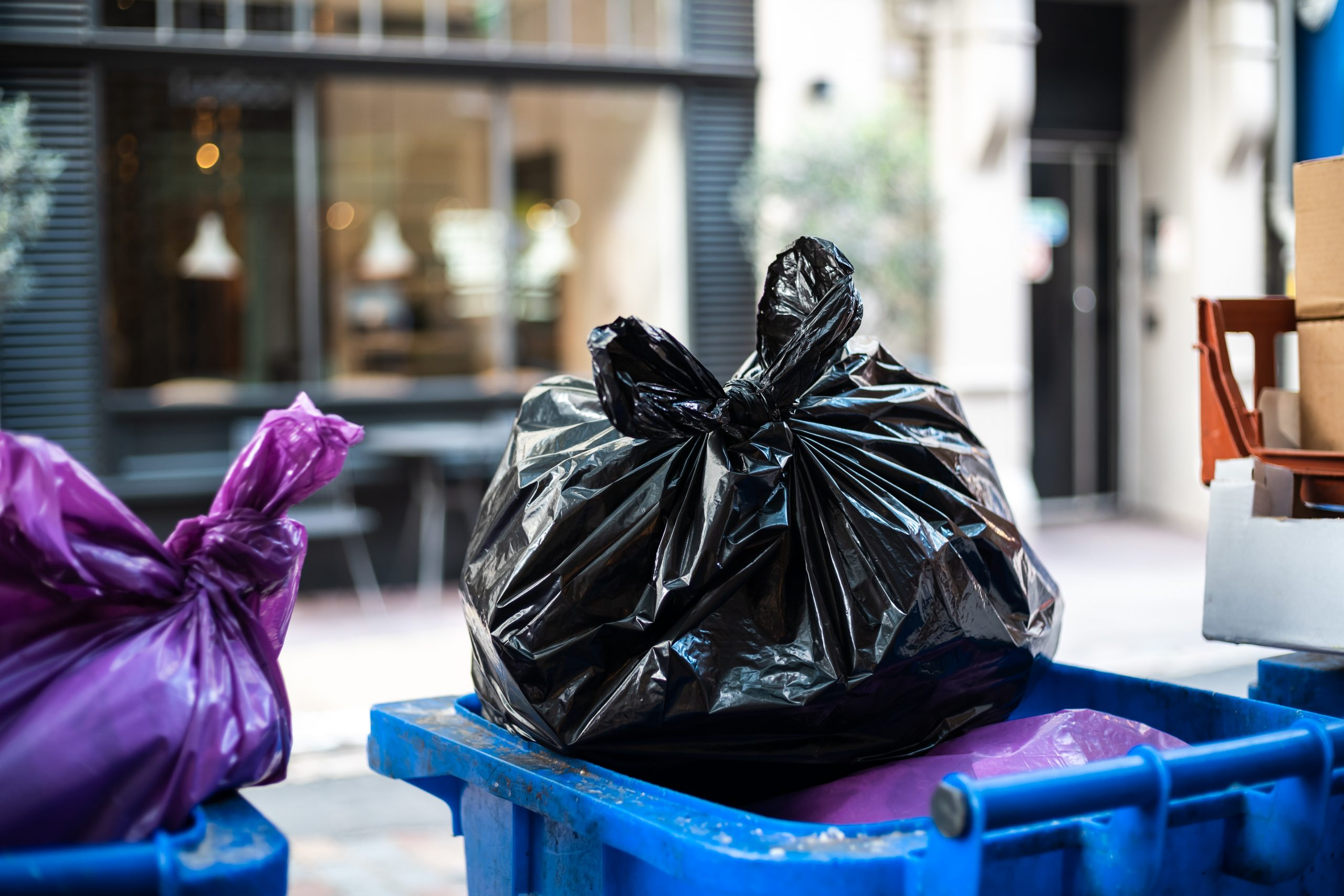 Purple and black bags of trash on a garbage bin during daytime